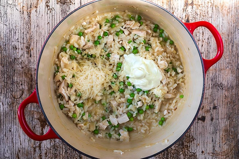 Chicken and Pea Risotto in a large cooking pot with cream and grated cheese