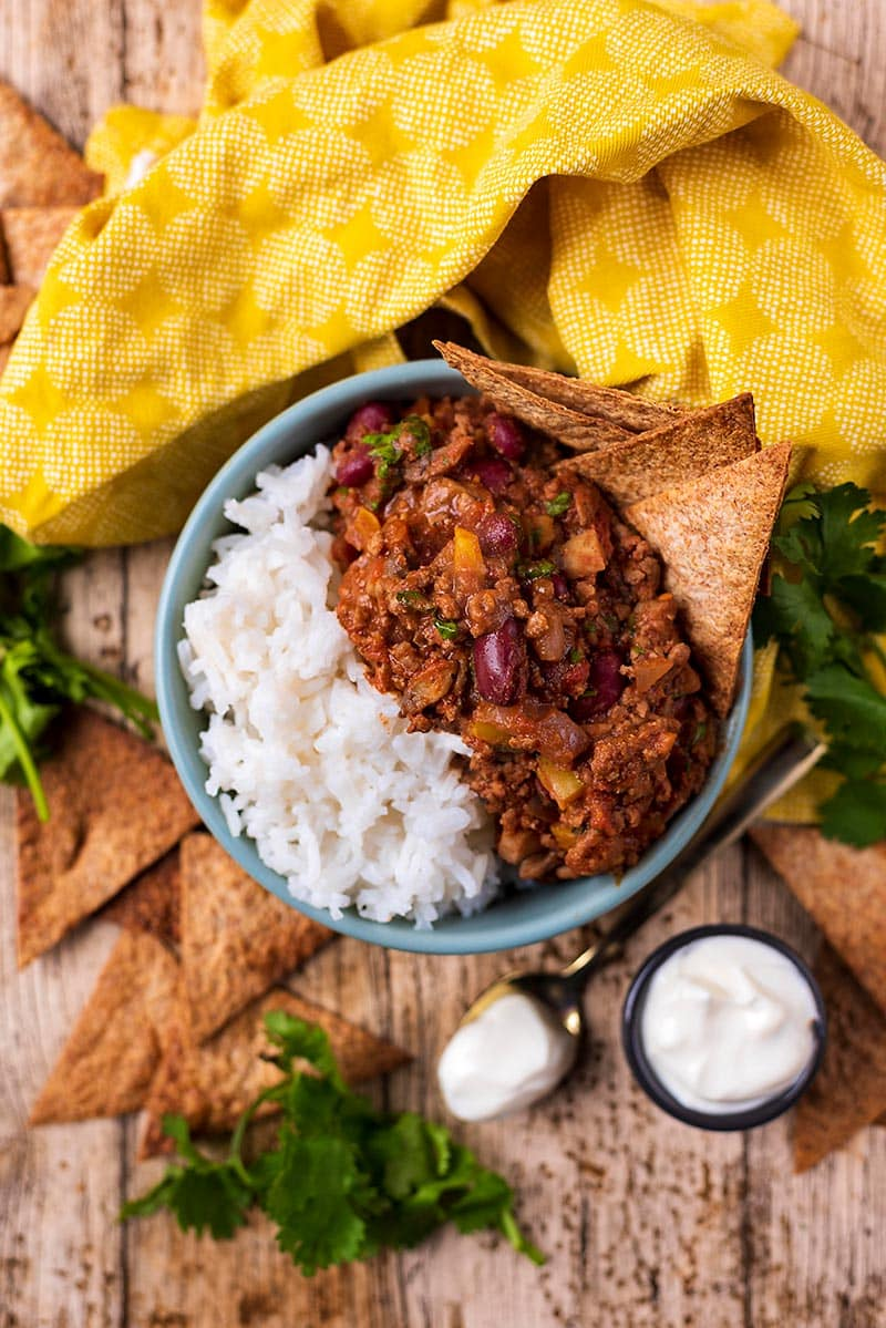 A bowl of chilli con carne and rice with tortilla chips sticking out of the chilli