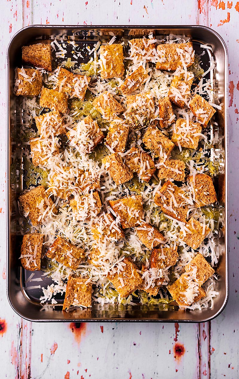 A baking tin full of croutons and grated Parmesan
