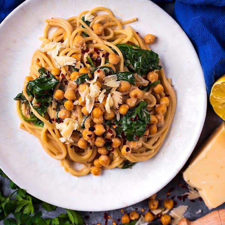 Easy Chickpea Pasta on a plate next to Parmesan cheese and lemon halves