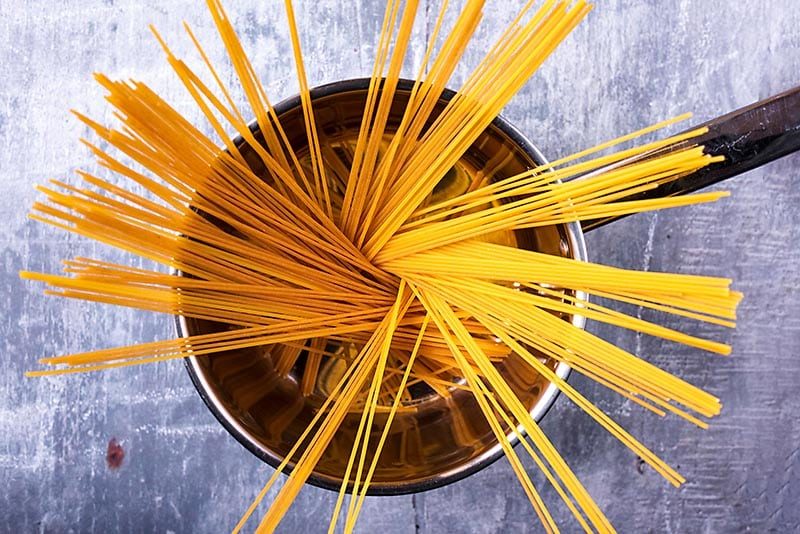 A saucepan with strands of spaghetti in it