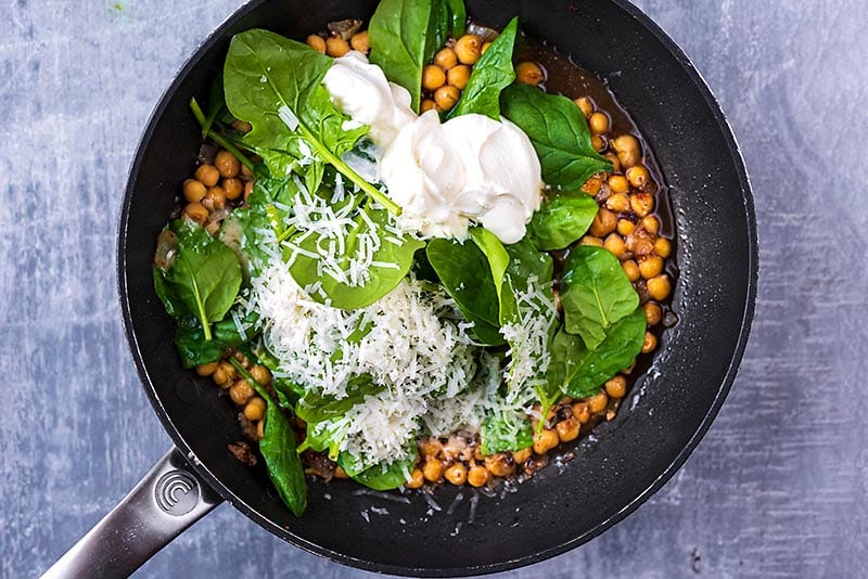 A fying pan containing onions, chickpeas, spinach, cream and cheese