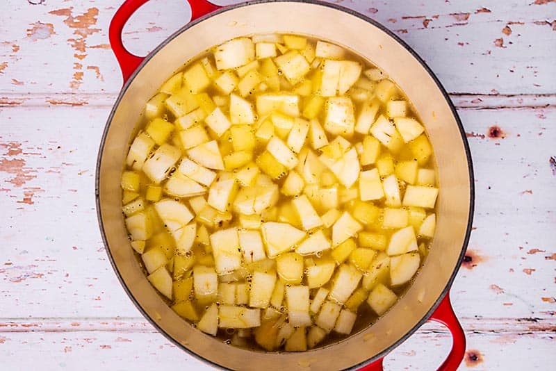 A large red pot containing diced parsnips and vegetable stock