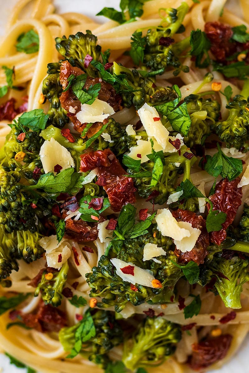 Pasta, broccoli and chopped tomatoes topped with shavings of Parmesan