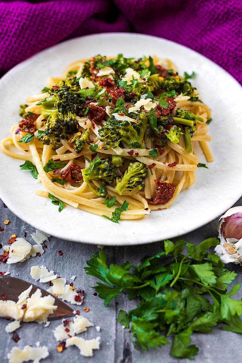 A plate of broccoli pasta next to some herbs and a bulb of garlic