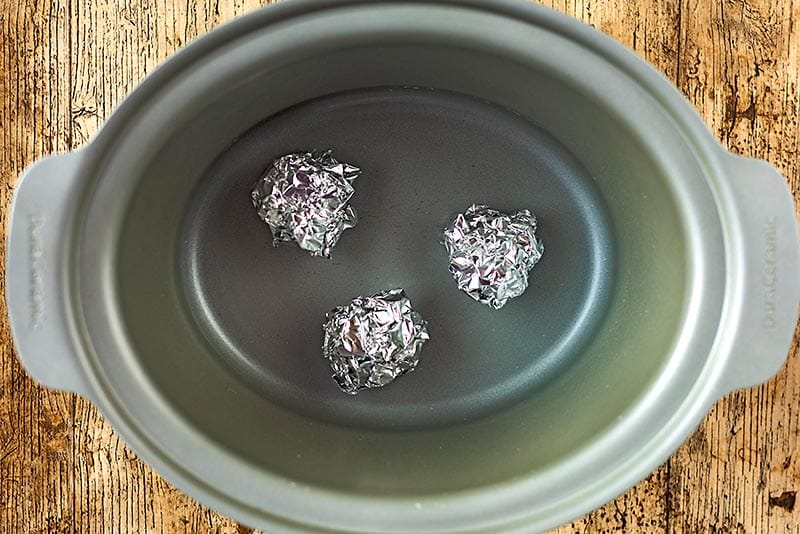 A slow cooker pot with three balls of aluminium foil in the bottom
