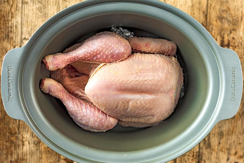 A slow cooker pot with a whole chicken in it