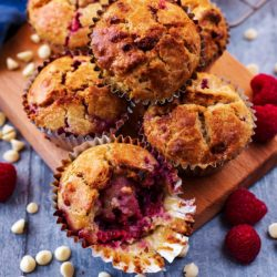 A pile of raspberry muffins on a wooden serving board
