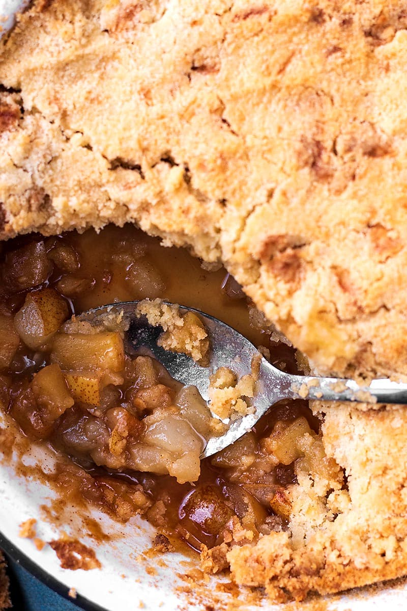 A crumble in a baking dish with a spoon in a scooped out area