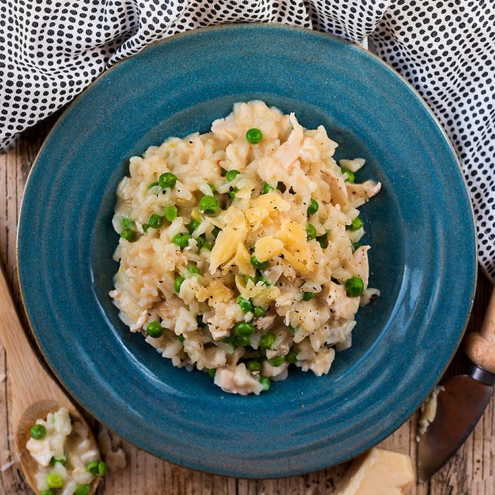Chicken and Pea Risotto in a blue bowl topped with shavings of Parmesan cheese