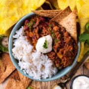 A bowl of chilli con carne and rice with a dollop of sour cream on top