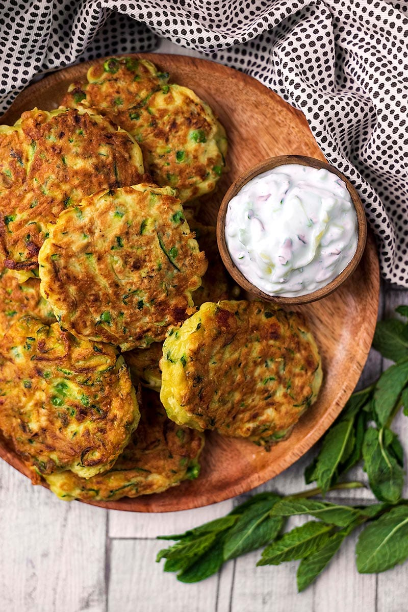 A plate of courgette fritters with a small dish of creamy tzatziki