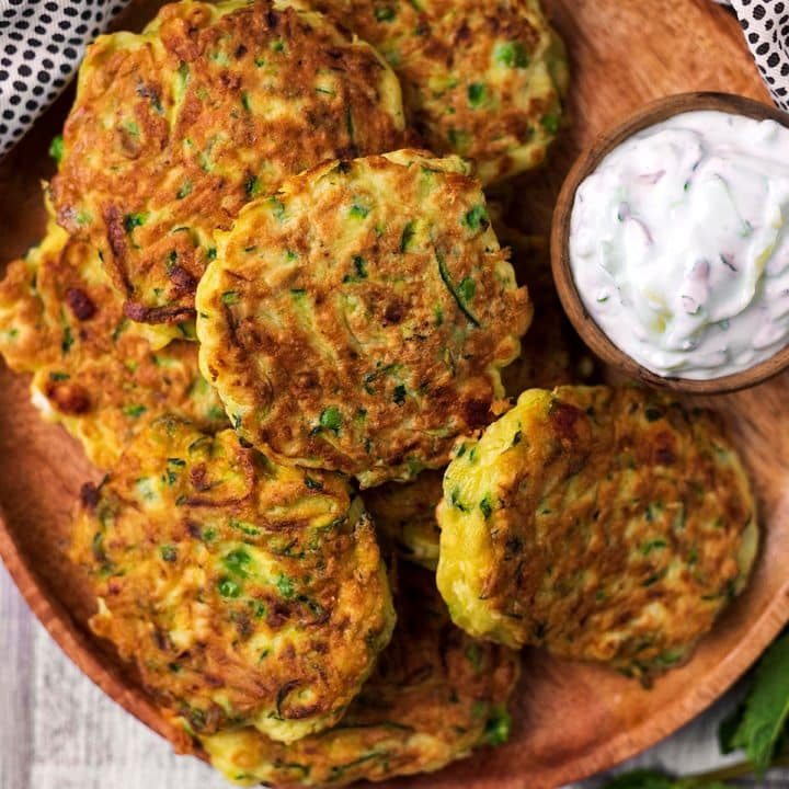 Easy Courgette Fritters on a wooden plate with a bowl of tzatziki