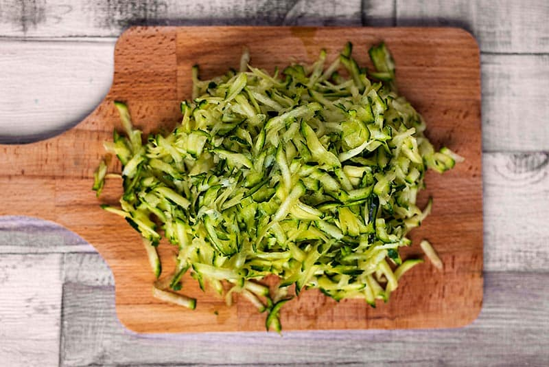 A chopping board with a pile of grated zucchini on it