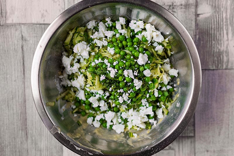 A mixing bowl containing grated zucchini, peas and feta