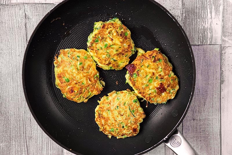 A frying pan with four courgette fritters cooking in it