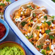 Fish Tacos in a serving dish next to guacamole and salsa