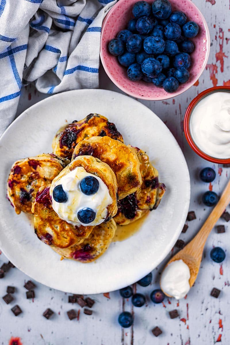 A plate of mini pancakes next to a bowl of blueberries and a bowl of yogurt