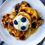 A plate of easy mini pancakes topped with a dollop of yogurt and some blueberries