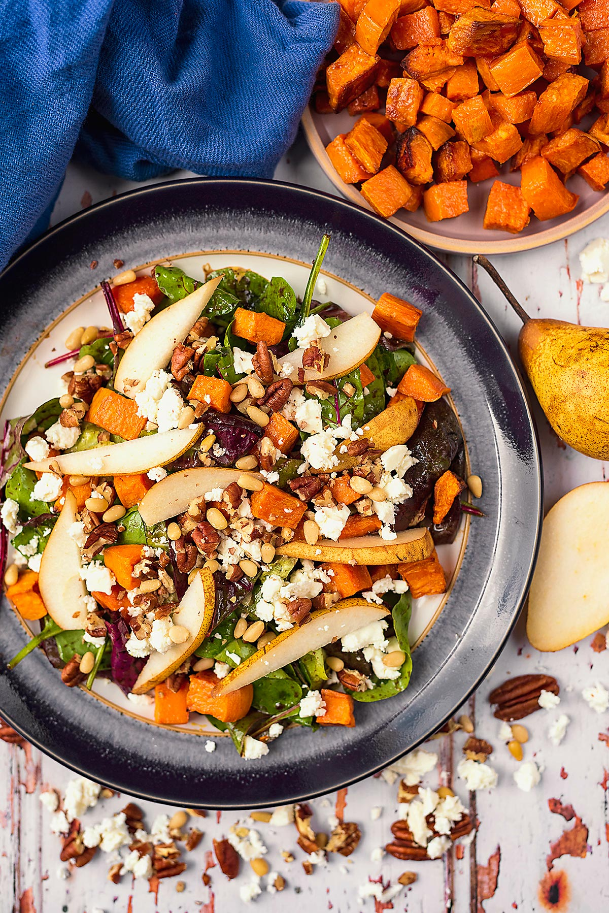 A plate of pear salad next to a bowl of roasted sweet potato cubes