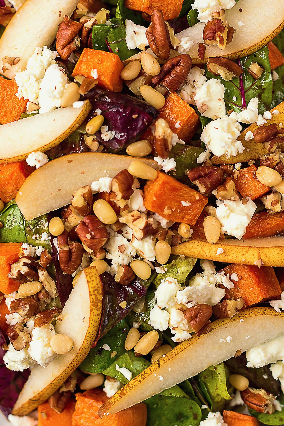 Salad leaves mixed with pear slices, sweet potato cubes and pine nuts