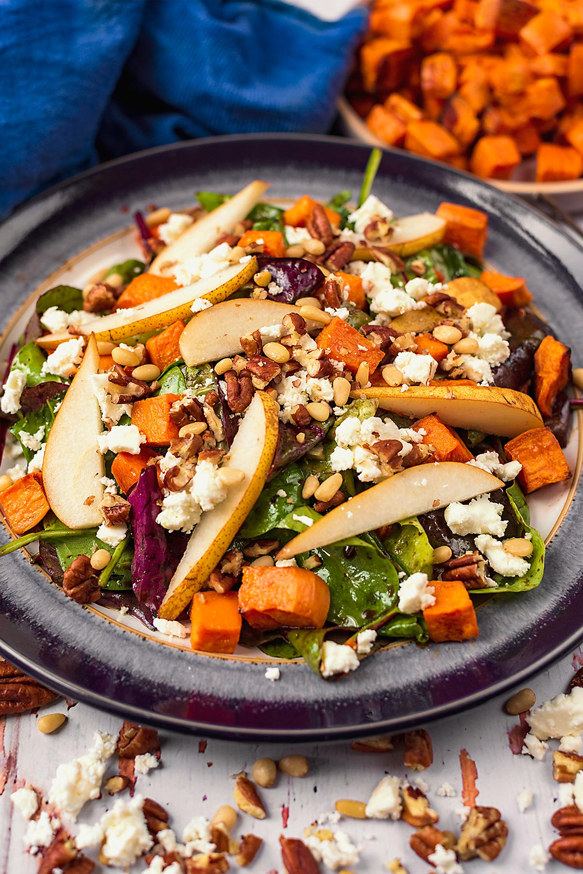 A plate of salad topped with sliced pears and cubes of sweet potato