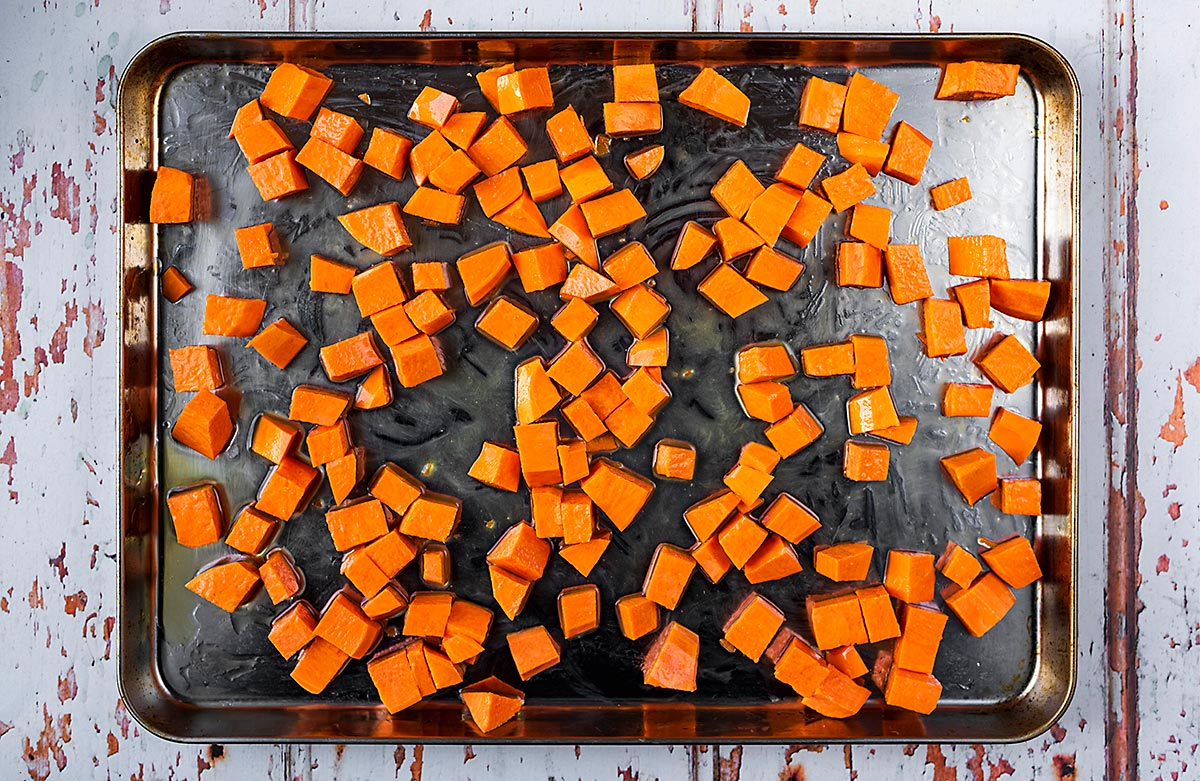 A large baking tray covered in cubes of roasted sweet potato