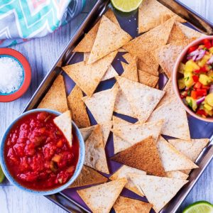 A metal tray covered in baked tortilla chips with two bowls of dip