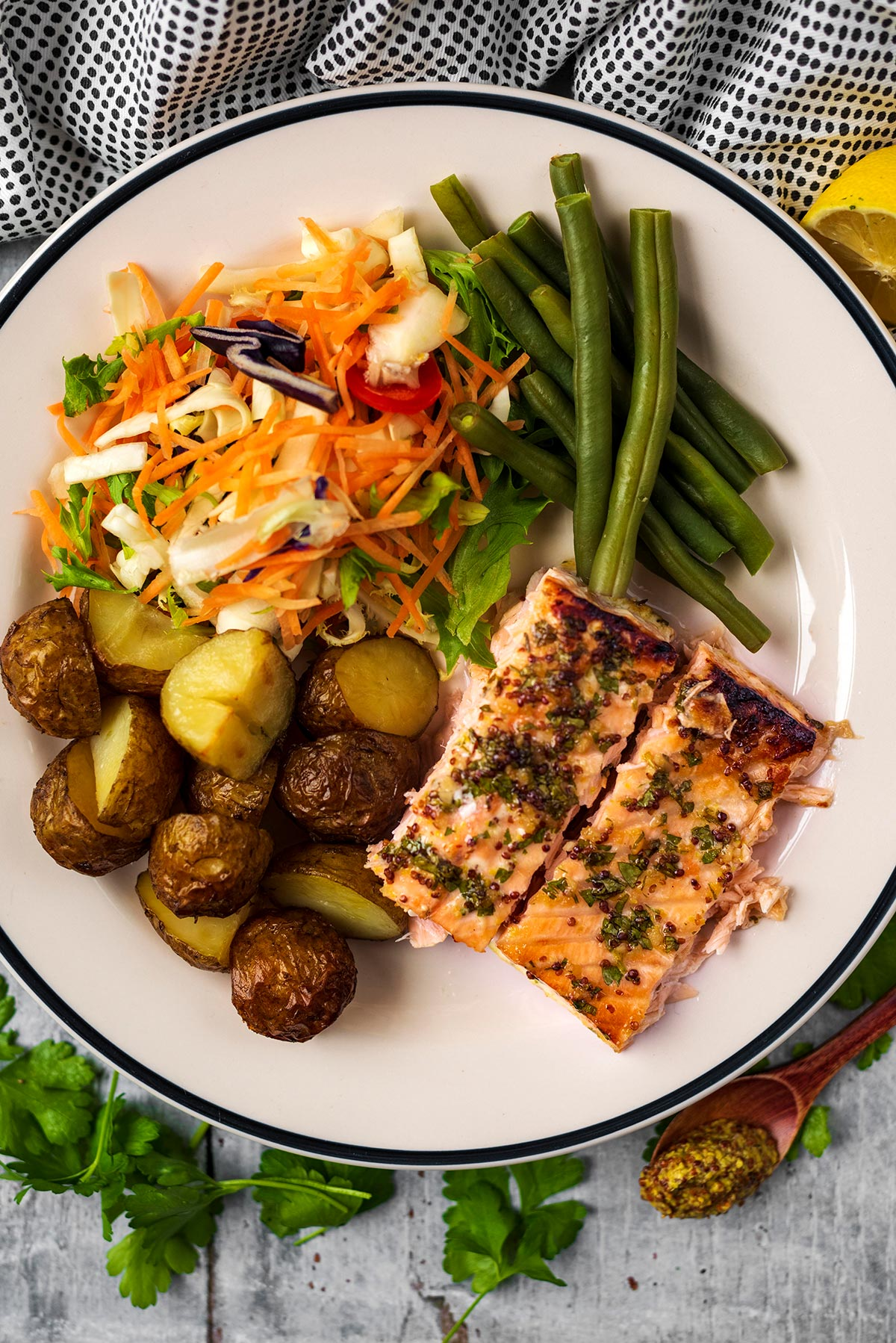 Two cooked salmon fillets on a plate with roasted potatoes, green beans and salad