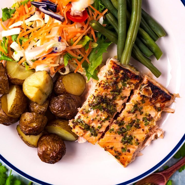 Honey Mustard Salmon on a plate with potatoes, beans and slaw