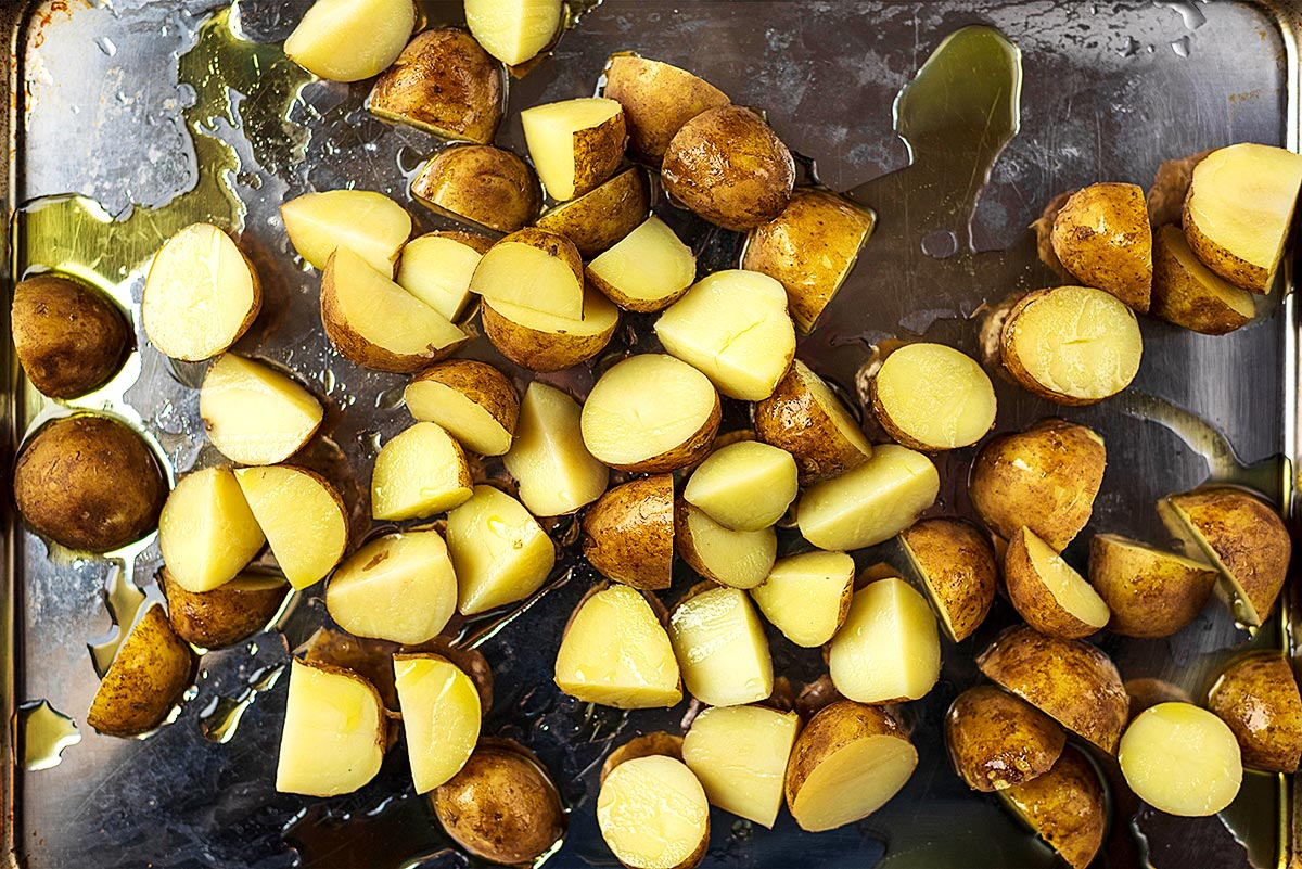 A baking tray full of new potatoes cut in half covered in oil