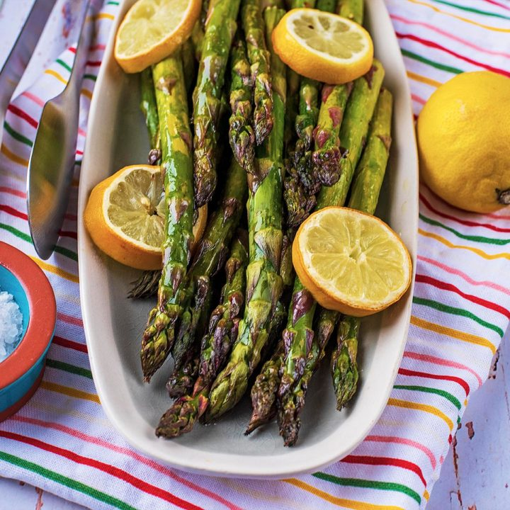 Roasted Lemon Asparagus on a long serving plate with lemon slices and a small pot of salt
