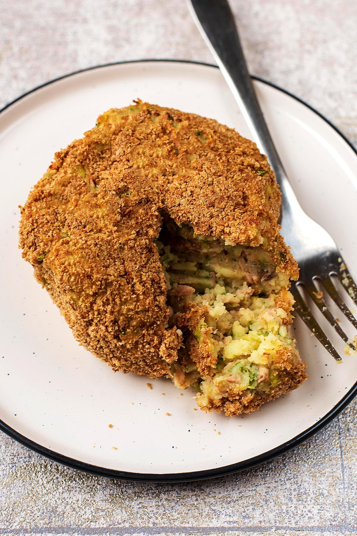 Tuna fish cake on a plate, cut open with a fork