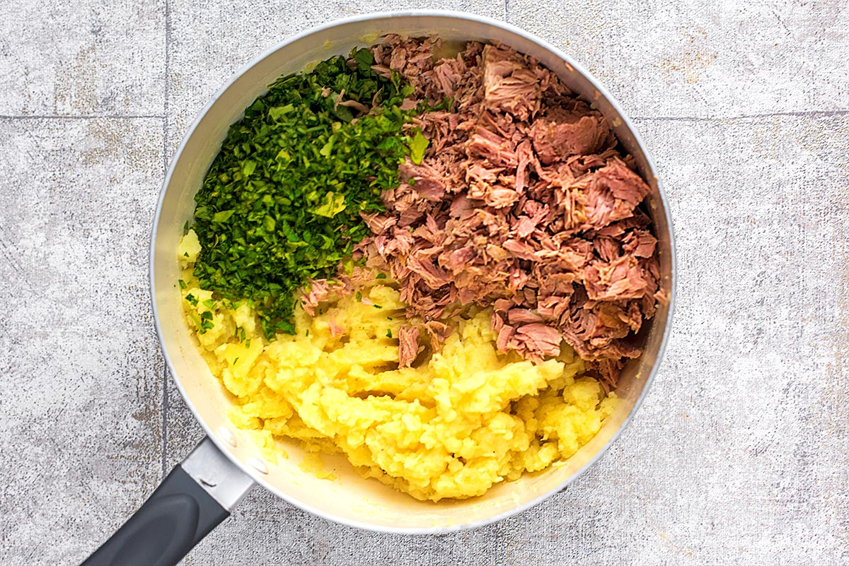 A saucepan with mashed potato, flaked tuna fish and chopped herbs