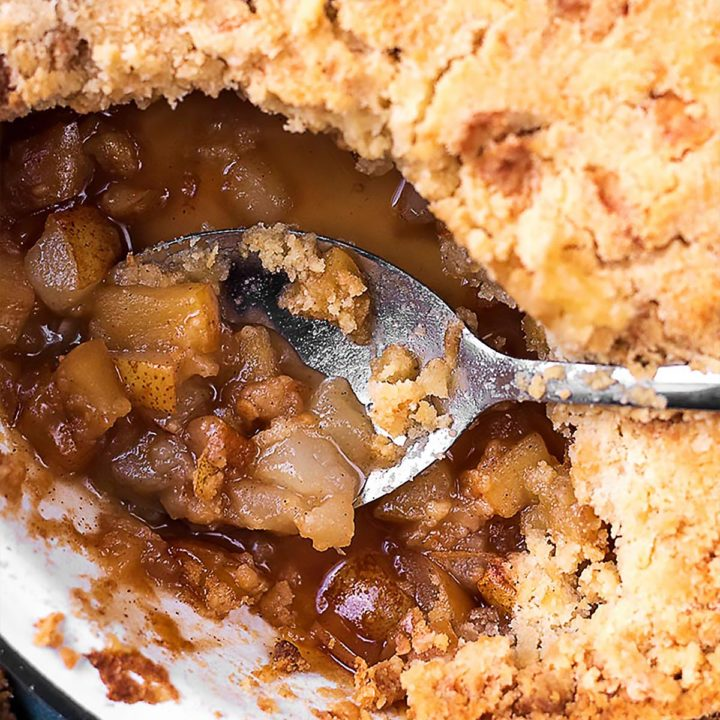 Apple and pear crumble with a spoon scooping some filling out