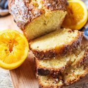 An orange drizzle cake cut into slices.