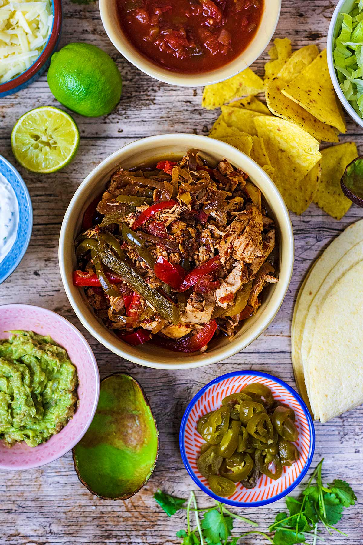 A bowl of fajita filling surrounded by salsa, guacamole, tortilla wraps, jalapenos and tortilla chips