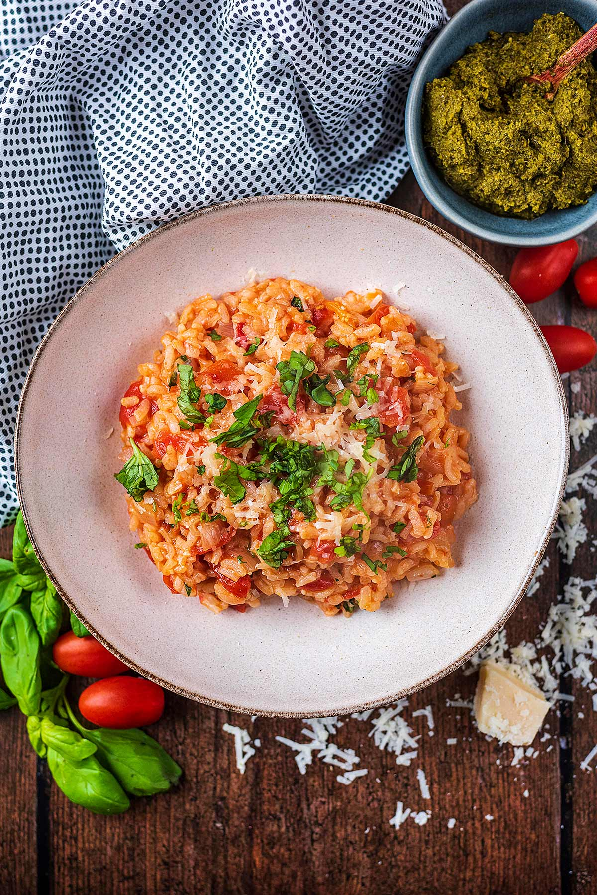 Tomato risotto in a large bowl next to a bowl of pesto.