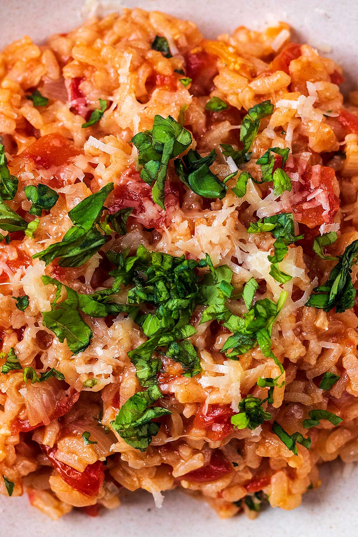 Tomato risotto with grated cheese and chopped herbs on top.