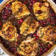 Cranberry chicken in sauce in a large dish topped with cranberries and thyme.