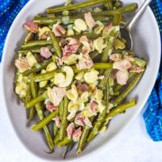 Slow cooker green beans in a bowl with a spoon.