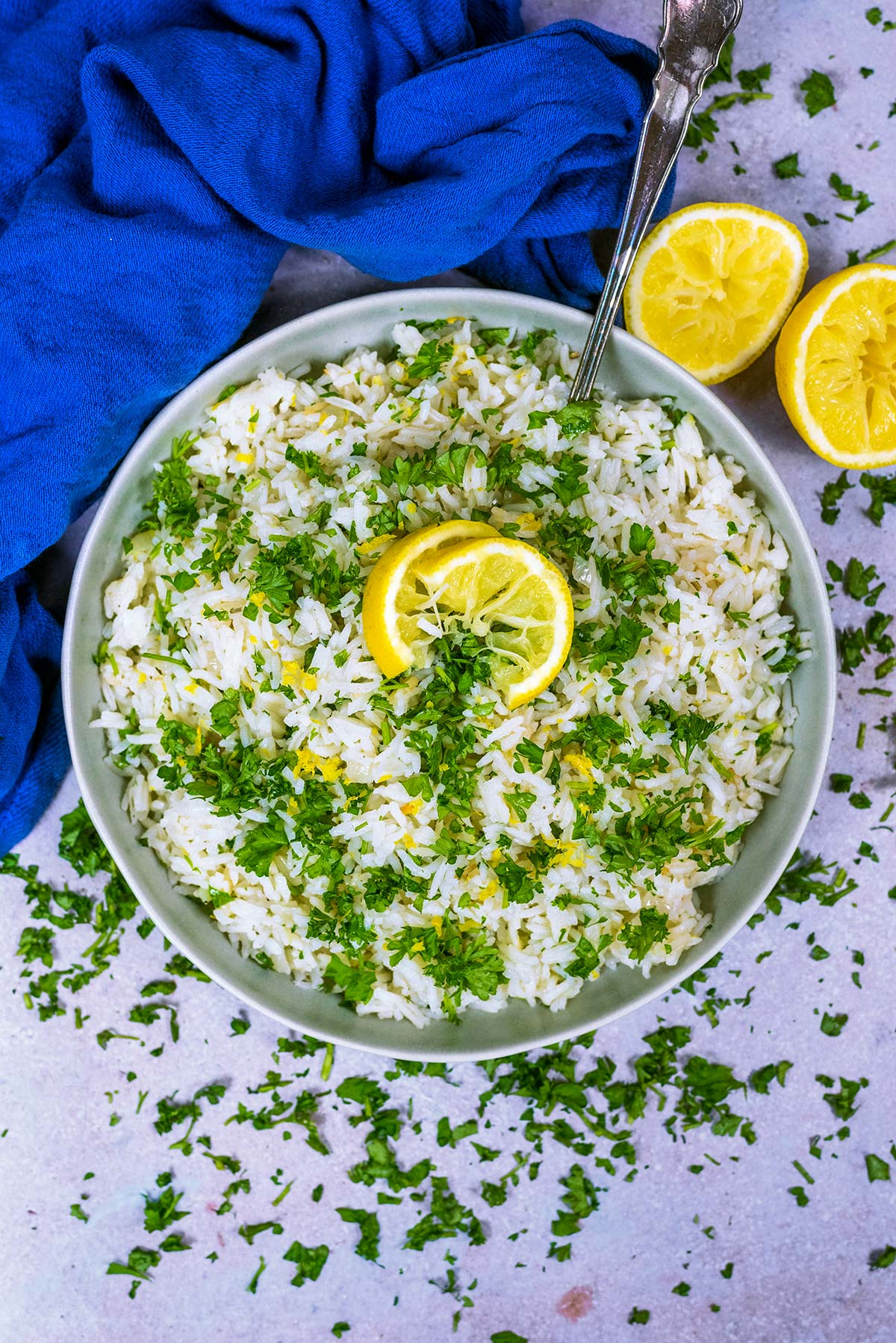 A large bowl of cooked rice, topped with chopped herbs and slices of lemon.