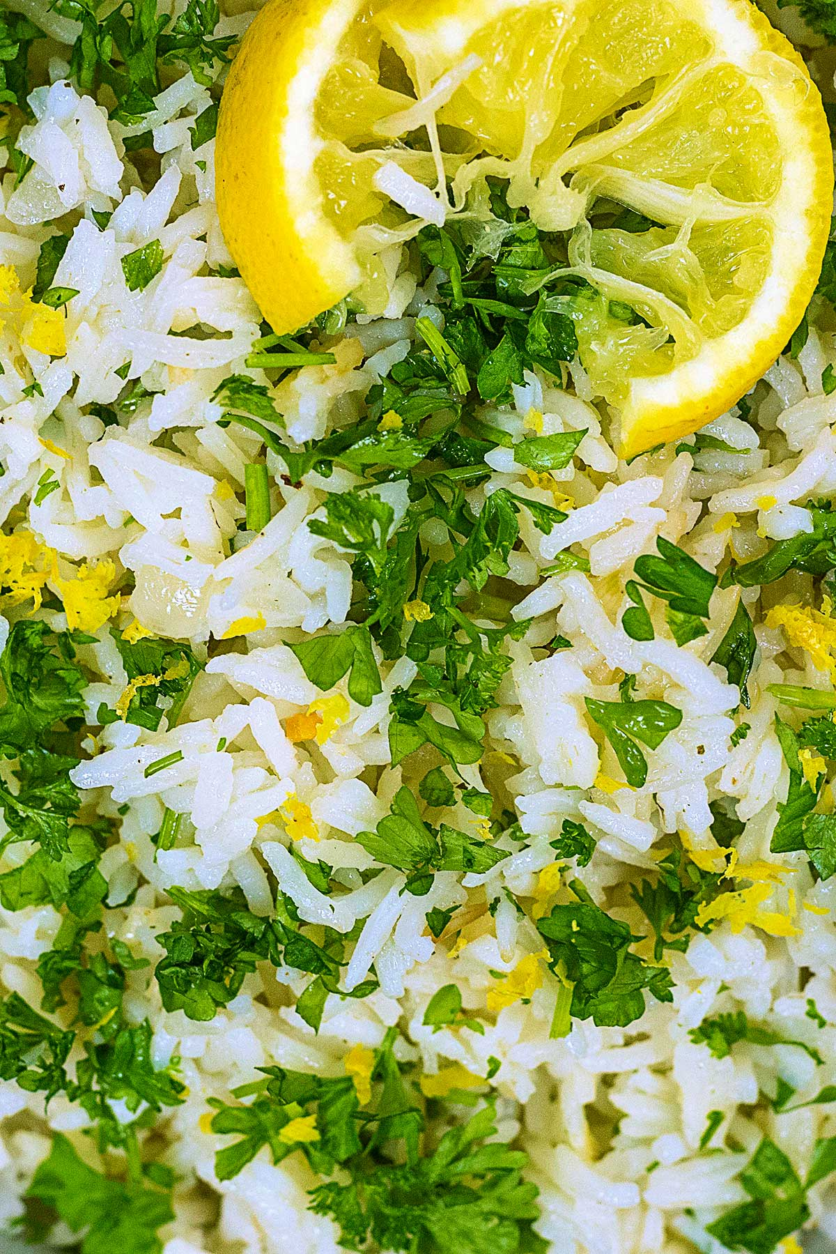 Cooked rice mixed with chopped parsley and lemon zest. A lemon slice is on top.