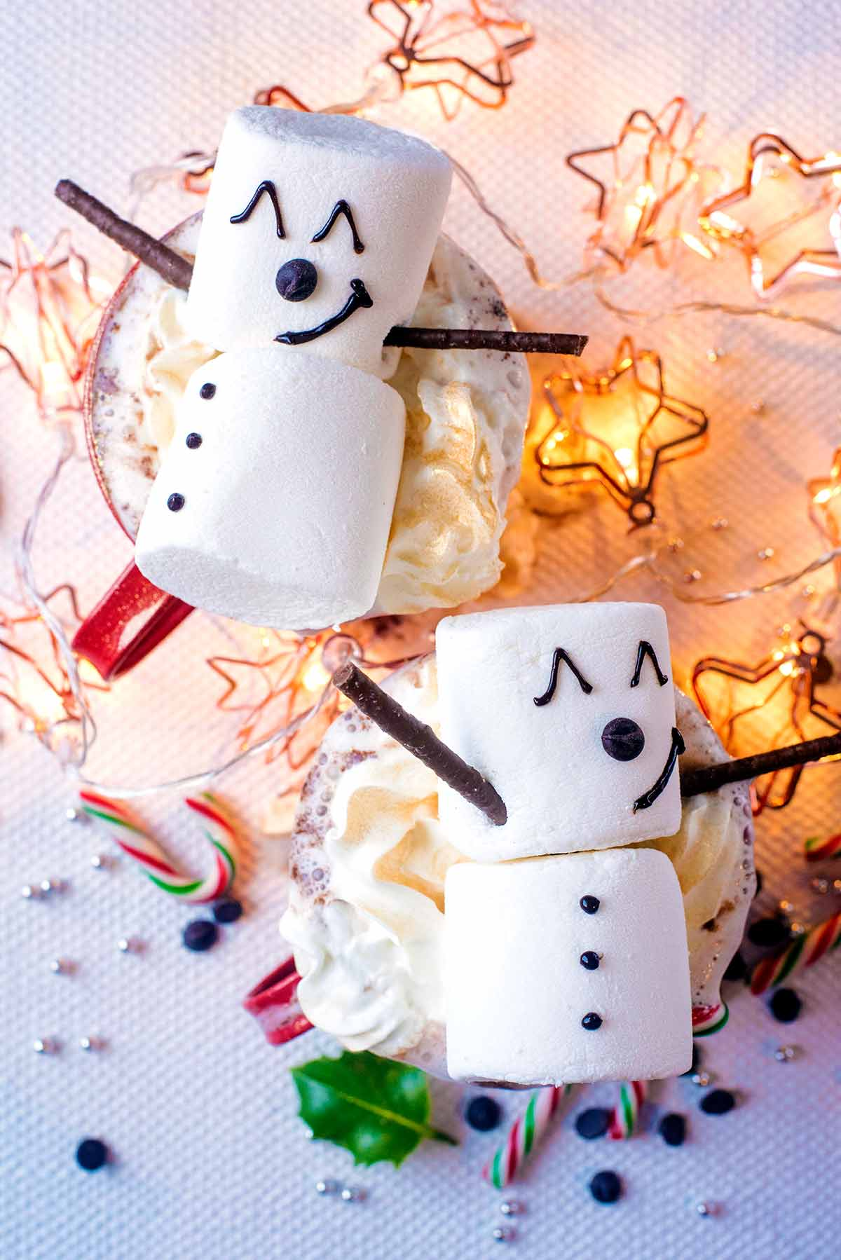 Marshmallows decorated like snowmen on top of mugs of hot chocolate.