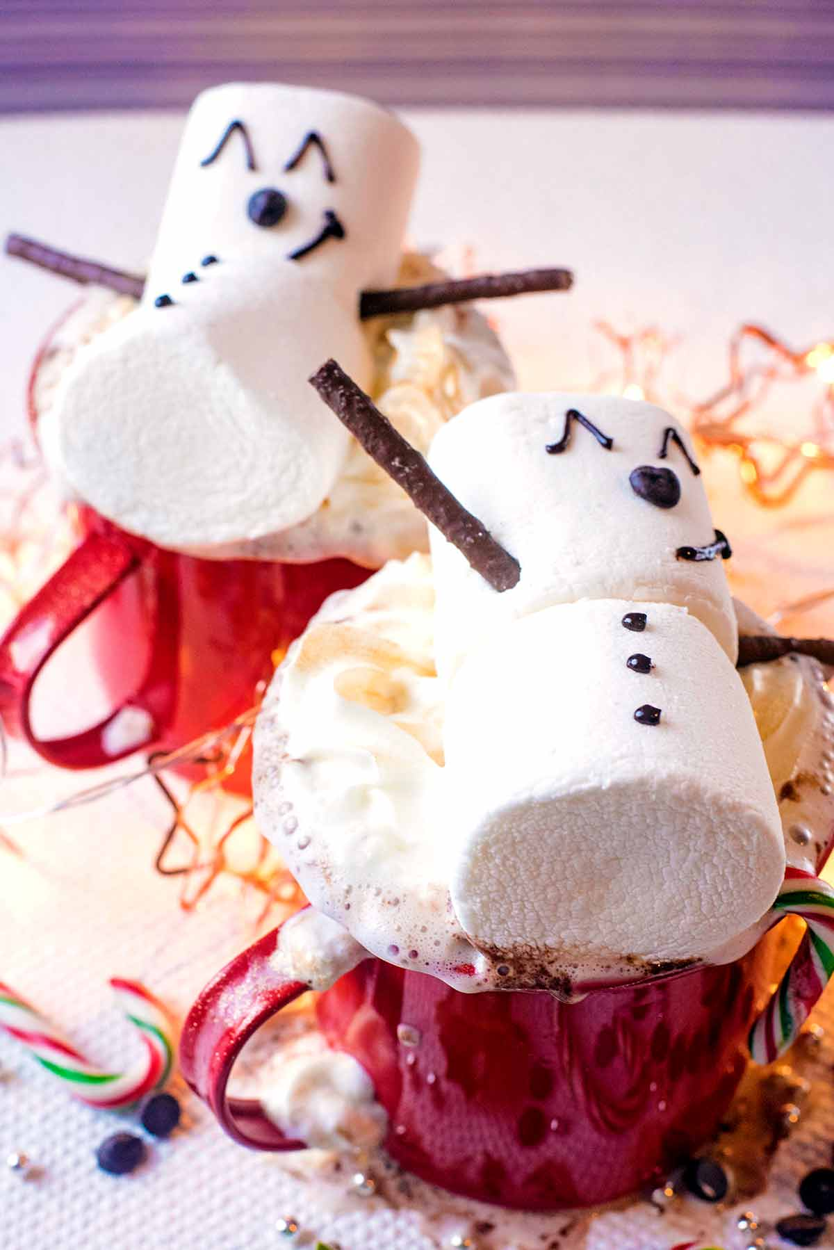 Two mugs of hot chocolate topped with cream and decorated with snowman marshmallows.
